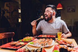 uomo che mangia sushi ordinato a domicilio